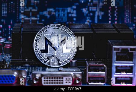 Front view of Monero cryptocurrency over computer video card. Bitcoin mining farm concept. - Stock Photo