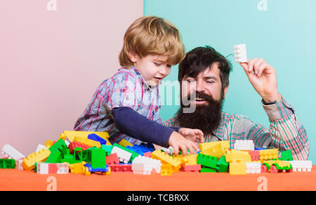 childrens day. child development. happy family. leisure time. father and son play game. building home with colorful constructor. little boy with bearded man dad playing together. happy childrens day. - Stock Photo