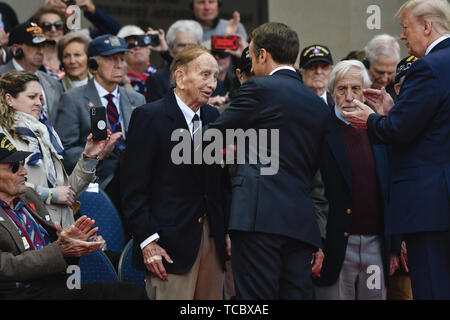 Colleville Sur Mer, France. 06th June, 2019. French President Emmanuel Macron, awardis the French National Order of Merit to a World War II veteran as U.S. President Donald Trump looks on during a commemoration ceremony marking the 75th D-Day Anniversary at the Normandy American Cemetery and Memorial June 6, 2019 in Colleville-sur-Mer, France. Thousands have converged on Normandy to commemorate the 75th anniversary of Operation Overlord, the WWII Allied invasion commonly known as D-Day. Credit: Planetpix/Alamy Live News - Stock Photo