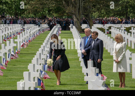 U.S. First Lady Melania Trump places flowers at the grave of an American service member buried at the Normandy American Cemetery as President Donald Trump/ French President Emmanuel Macron and his wife Brigitte Macron look on during a commemoration ceremony marking the 75th D-Day Anniversary at the Normandy American Cemetery and Memorial June 6, 2019 in Colleville-sur-Mer, France. Thousands have converged on Normandy to commemorate the 75th anniversary of Operation Overlord, the WWII Allied invasion commonly known as D-Day. - Stock Photo