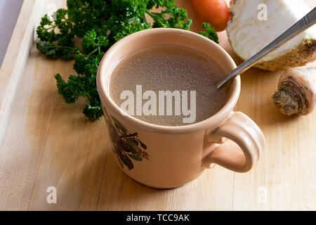 Chicken stock in a vintage mug with a spoon, with parsley, carrot and celery root in the background.