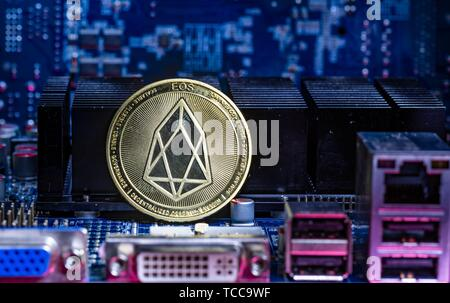 Front view of Eos cryptocurrency over computer video card. Bitcoin mining farm concept. - Stock Photo