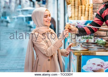 Beautiful Muslim woman in headscarf and fashionable modern clothes laughes because of Ice cream seller man playing traditional Turkish joke. Modern - Stock Photo