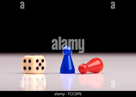 Standing blue playing figurine as winner and lying red figurine as loser with playing dice on white table top with black background. Space for your te