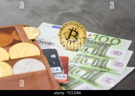 View of metal bitcoins and VISA credit cards in brown leather wallet and over Euro banknotes. Concept image for cryptocurrency. - Stock Photo