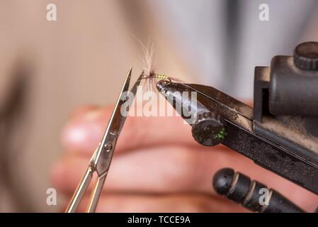 Close up of fisherman tying a fly for fishing. - Stock Photo