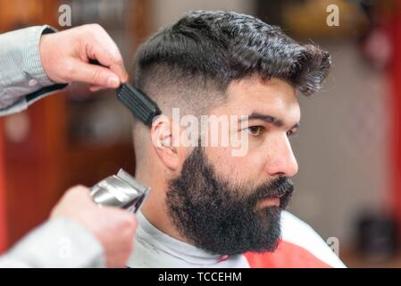 Handsome bearded man, getting haircut by barber, with electric trimmer at barbershop. - Stock Photo