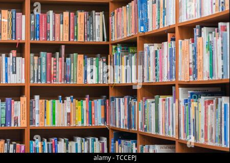 Bookshelf in public library, side angle view, horizontal. - Stock Photo
