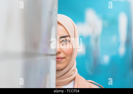 Beautiful Muslim woman in headscarf and fashionable modern clothes hides half face at wall with blue background. - Stock Photo