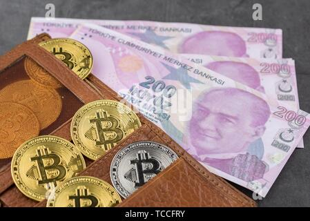 View of metal bitcoins in brown leather wallet and over Turkish Lira banknotes. Concept image for cryptocurrency. - Stock Photo