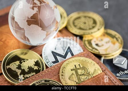 View of different kind of metal bitcoins in brown leather wallet and glass globe. Concept image for cryptocurrency. - Stock Photo