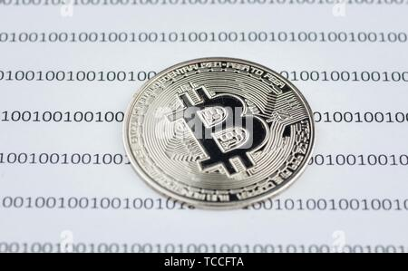 Bitcoin, cryptocurrency physical coin on paper with binary system of zeros and ones. Virtual cryptocurrency concept. Concept image for cryptocurrency. - Stock Photo