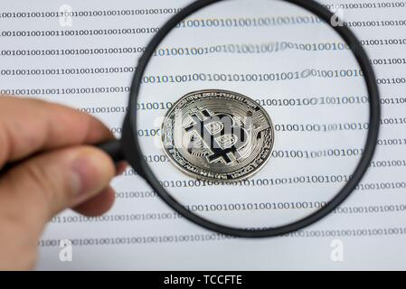 Man hand holds magnifying glass over bitcoin, cryptocurrency physical coin on paper with binary system of zeros and ones. Virtual cryptocurrency - Stock Photo