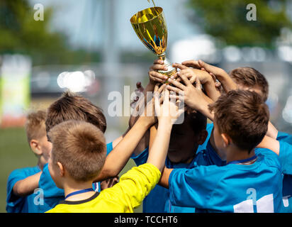 Happy Sports Soccer Team Raising Trophy. Winners of Youth Football Tournament - Stock Photo