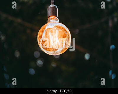 Image of glowing light bulb on dark background, close up - Stock Photo