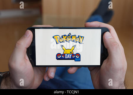 LOS ANGELES, CALIFORNIA - JUNE 3, 2019: Lying Man holding a smartphone and playing the Pokemon Go game on the smartphone screen. An illustrative edito