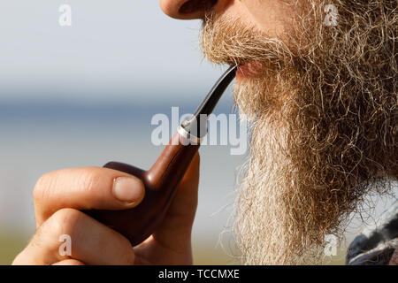 Bearded man holding a smoking pipe in his mouth, side view - Stock Photo