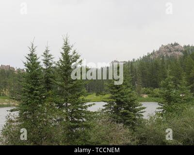 Lush trees surrounding beautiful Sylvan Lake, Custer State Park, South Dakota. - Stock Photo
