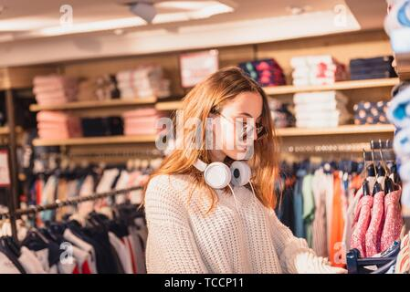 Beautiful attractive young girl in jumper with headphone and sunglasses chooses clothes thinking looking at clothing while shopping in store. - Stock Photo