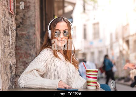 Beautiful attractive young trendy girl with headphones,smartphone and sunglasses sits at a street cafe while drinking fruit juice. - Stock Photo
