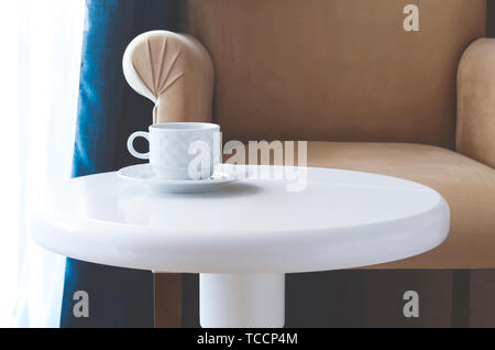 White tea cup and saucer on a round white table against a beige chair - Stock Photo