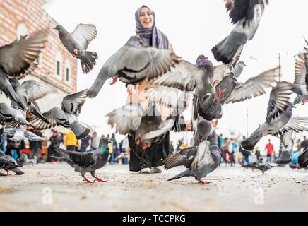 Beautiful young happy Muslim woman in headscarf and fashionable trendy clothes feeds pigeons with wheat. - Stock Photo
