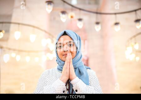 Muslim woman in headscarf and hijab prays while clasping her hands with mosque on background. Religion praying concept. - Stock Photo