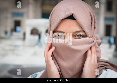 Beautiful Muslim woman in headscarf and fashionable modern trendy clothes covers her face with scarf with Mosque at background. Modern Muslim women - Stock Photo