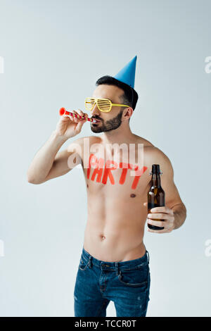 Shirtless man with party blower holding bottle of beer isolated on grey - Stock Photo