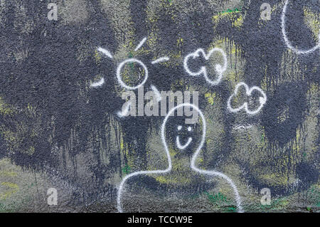 Children's drawing of a smiling man with sun and clods drawn on the wall of a building - Stock Photo