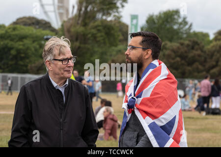 Two men talking at an outdoor event one of the men has a union jack flag wrapped around his body - Stock Photo