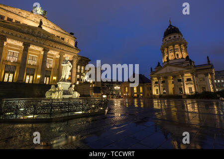 Illuminated Schiller Monument, Konzerthaus Berlin and Französischer Dom (French Cathedral) at the Gendarmenmarkt Square in Berlin, Germany, at dusk. - Stock Photo
