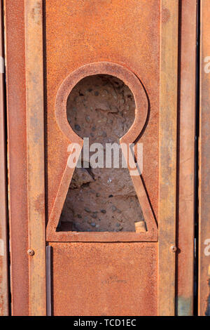 Large keyhole in a rusted metal door with a view of the rock wall behind - Stock Photo