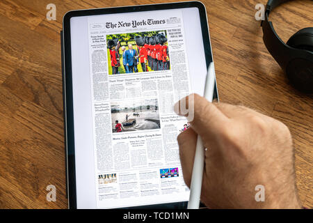 Paris, France - Jun 6, 2019: Man reading on Apple iPad Pro the New York Times newspaper about Donald Trump United States presidential visits to the United Kingdom and Ireland - Stock Photo