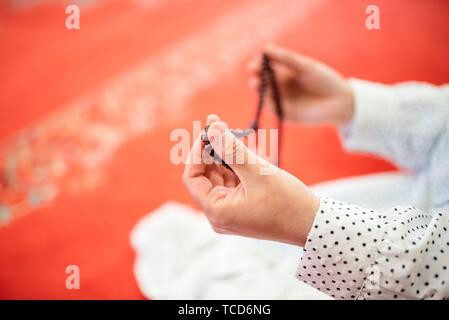 Close up view of a Muslim woman hands in hijab while holding rosary with her hands and praying. Religion praying concept. - Stock Photo