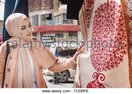 Beautiful Muslim women in headscarf and fashionable modern trendy clothes buys Traditional Turkish rug and carpets. Muslim women lifestyle travel - Stock Photo