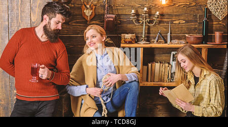 Friends or family spend pleasant evening in gamekeepers house, interior background. Girls and man on smiling faces enjoy cozy atmosphere while having rest. Coziness concept. Family enjoy vacation. - Stock Photo