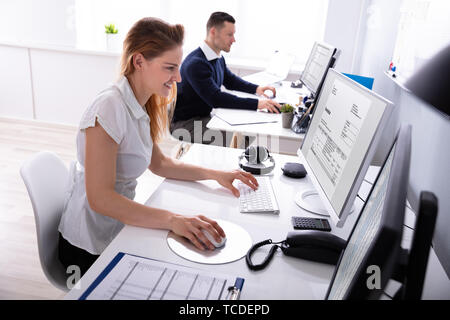 Smiling Young Businesswoman Checking Invoice On Computer At Workplace - Stock Photo