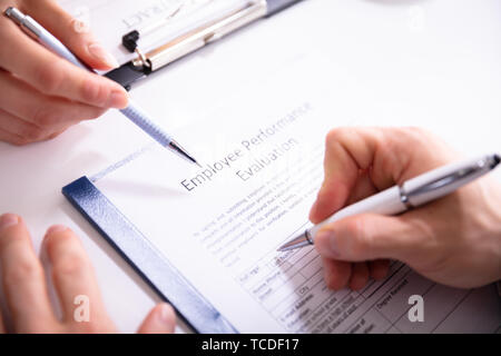 Close-up Of A Person Filling Performance Evaluation Form Of Employee Over Desk - Stock Photo