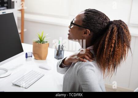 Businesswoman Suffering From Shoulder Pain While Working In Office - Stock Photo