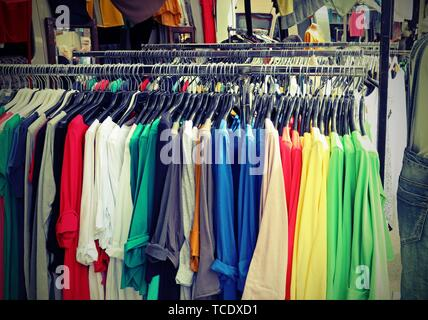 stand of used clothes at outdoor flea market - Stock Photo