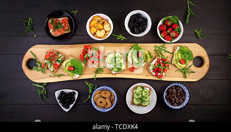 Flat lay of healthy vegetarian dinner table setting. Sandwiches with tomato, cucumber, avocado, strawberry, herbs and olives, snacks. Clean eating, ve - Stock Photo