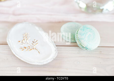 Sweet french macaroons on wood flat lay copyspace. Top voew on set of three purple macaroons on wooden board, lying diagonally on wooden table, void - Stock Photo