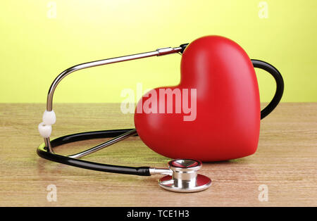 Medical stethoscope and heart on wooden table on green background - Stock Photo
