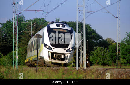 Fast electric train on tracks. Modern passenger rail transport in Europe. - Stock Photo