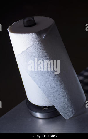 A metallic paper towel holder with a white roll of paper towels on a stainless steel table - Stock Photo