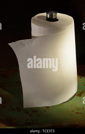 A metallic paper towel holder with a white roll of paper towels on a rusty old table - Stock Photo