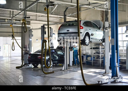 Two used cars with an open hood raised on a lift for repairing the chassis and engine in a vehicle repair shop. Auto service industry. - Stock Photo
