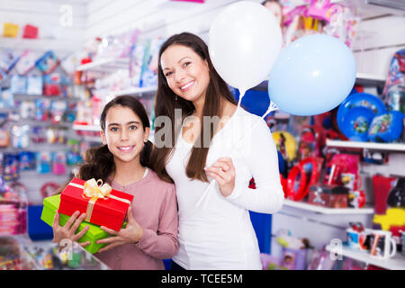 Portrait of happy mother and daughter holding gifts and balloons in store - Stock Photo