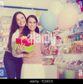 Portrait of smiling mother and daughter holding gifts and balloons in store - Stock Photo